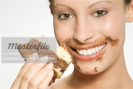 700-02038099 © Picup Pictures Model Release: Yes Property Release: No Model Release Woman With Chocolate on Her Face Eating Cake