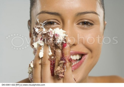 portrait-of-a-young-woman-eating-cake-icing-and-smiling